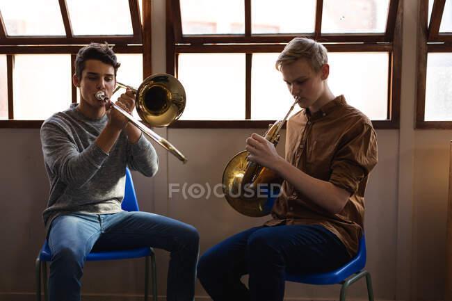 Vue de face de deux adolescents caucasiens assis devant une fenêtre jouant un trombone et un cor français — Photo de stock