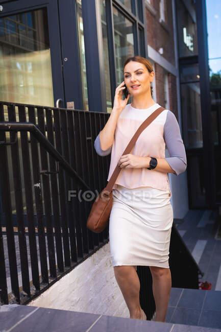 Кавказская деловая женщина в солнечный день, идет по лестнице, разговаривает по смартфону и носит смартфоны — стоковое фото