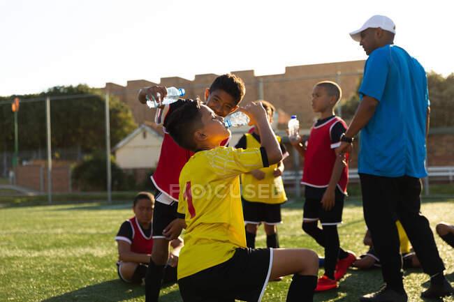Vista lateral de un entrenador de fútbol masculino de raza mixta de pie e instruyendo a un grupo multiétnico de jugadores de fútbol masculino en un campo de juego bajo el sol, refrescarse y beber agua durante una sesión de entrenamiento de fútbol - foto de stock
