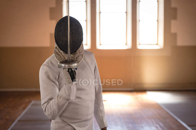 African American sportsman wearing protective fencing outfit during a fencing training session, preparing for a duel, holding an epee in front of face. Fencers training at a gym. — Stock Photo