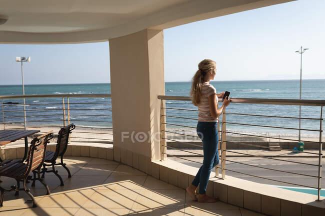 Kaukasische Frau, die auf einem Balkon steht, ein Smartphone in der Hand hält und wegschaut. Soziale Distanzierung und Selbstisolierung in Quarantäne. — Stockfoto