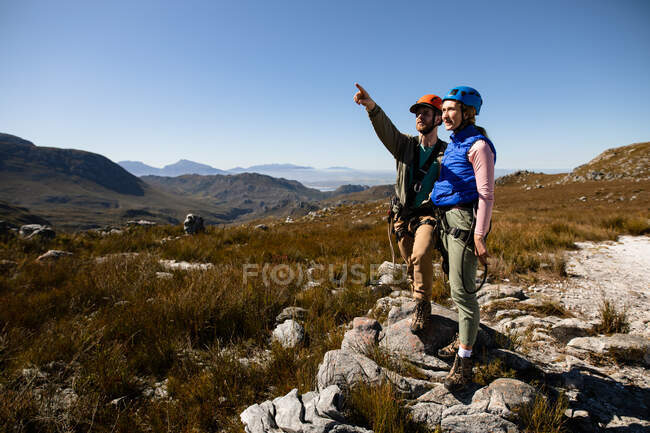 Front view of Caucasian couple enjoying time in nature together, wearing zip lining equipment, standing and admiring the view, the man is pointing on a sunny day in mountains — Stock Photo