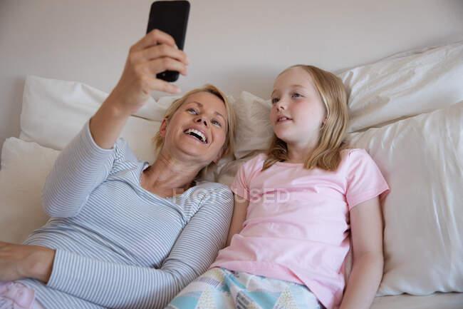 Передній вид на кавказьку жінку, яка проводить сімейний час зі своєю донькою вдома, лежачи на ліжку у своїй спальні, посміхаючись і беручи селфі зі своїм смартфоном. — стокове фото