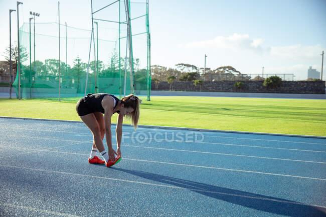 Вид сбоку на кавказскую спортсменку, практикующую на спортивном стадионе, растягивающуюся, наклоняющуюся, чтобы коснуться пальцев ног. Лёгкая атлетика на стадионе. — стоковое фото