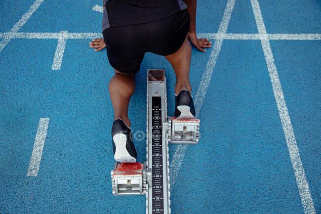 Высокоугольный крупный план спортсмена-мужчины, практикующего на спортивном стадионе, в позиции на стартовых блоках, готовящегося к спринту — стоковое фото