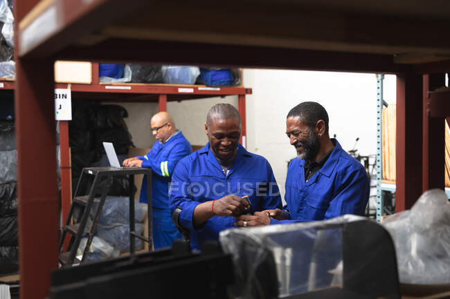 Two African American male workers in a storage warehouse at a factory making wheelchairs, standing and talking, checking parts on shelves — Stock Photo
