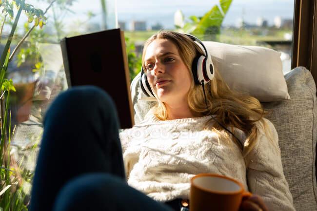 Vista frontale da vicino di una donna caucasica seduta nel suo soggiorno di fronte a una finestra in una giornata di sole, leggendo un libro e indossando cuffie — Foto stock