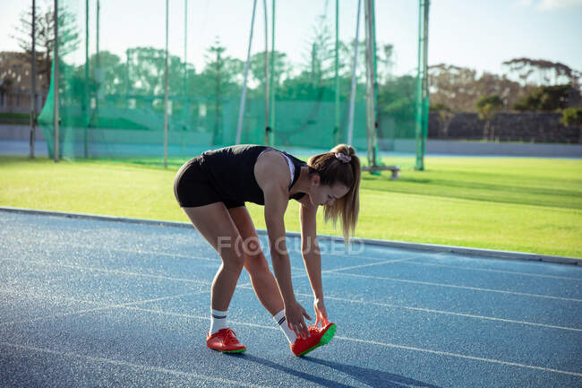 Кавказька спортсменка, яка тренується на спортивному стадіоні, розтягується, згинаючись на біговій доріжці, щоб торкнутися пальців ніг. — стокове фото