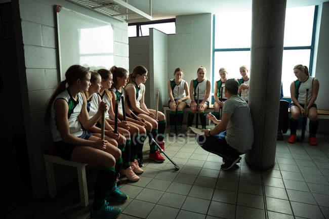 Вид сбоку на кавказского тренера по хоккею на траве, взаимодействующего с группой кавказских хоккеистов, сидящего в раздевалке, показывающего им план игры — стоковое фото