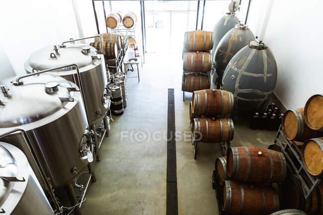 Vista ad alto angolo di un piccolo birrificio vano di fermentazione e stoccaggio con vasche e botti di legno poste lungo le pareti. — Foto stock