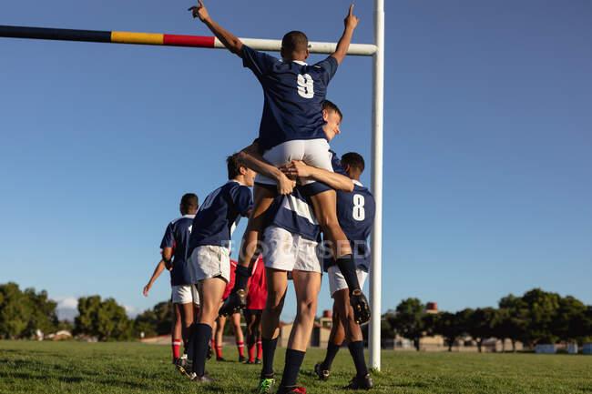 Vista trasera de un jugador de rugby masculino caucásico adolescente con tira de equipo azul y blanco, levantando a su compañero de carrera mixta, celebrando una victoria con los brazos levantados en el aire, en un campo de juego durante un partido de rugby - foto de stock