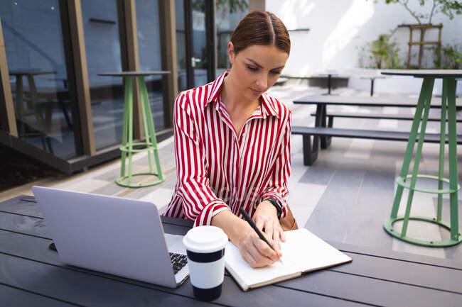 Кавказская деловая женщина на ходу в солнечный день, сидит за столом и делает заметки, с кофе на вынос и ноутбуком на столе — стоковое фото
