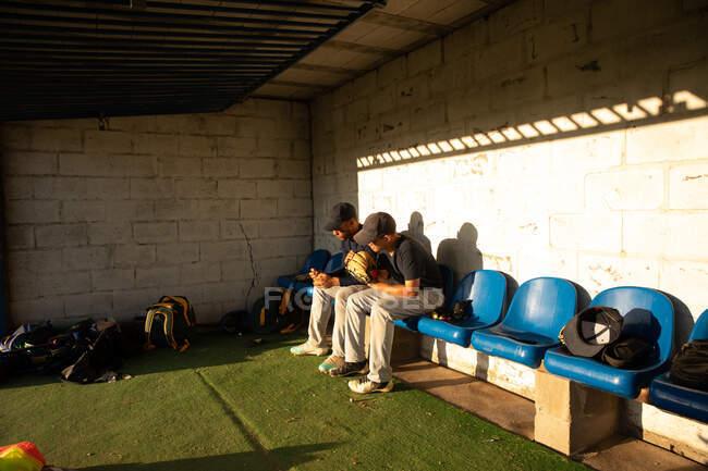 Seitenansicht von zwei gemischten männlichen Baseballspielern, während eines Baseballspiels an einem sonnigen Tag, auf einer Bank sitzend, nach unten schauend, sich auf ein Feld vorbereitend — Stockfoto