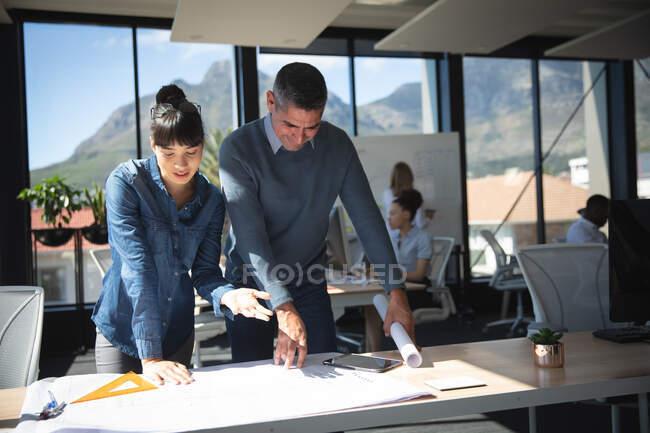Eine asiatische Geschäftsfrau und ein kaukasischer Geschäftsmann arbeiten in einem modernen Büro, stehen am Schreibtisch, betrachten Pläne und sprechen, während ihre Kollegen im Hintergrund arbeiten. — Stockfoto