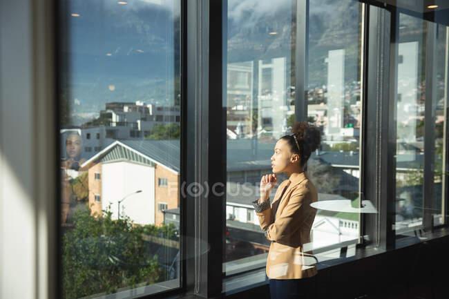 Деловая женщина смешанной расы, работающая в современном офисе, глядящая в окно, трогающая подбородок и думающая, в солнечный день — стоковое фото