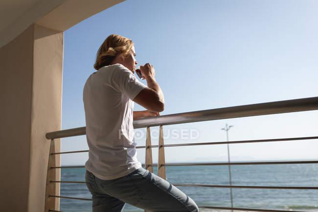 Белый мужчина стоит на балконе, пьет чашку кофе. Социальное дистанцирование и самоизоляция в карантинной изоляции. — стоковое фото