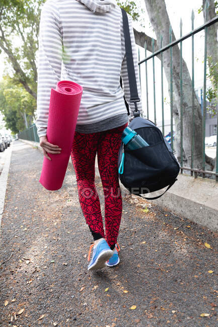 Rear view low section of a fit woman on her way to fitness training on a cloudy day, carrying sports bag and a yoga mat — Stock Photo