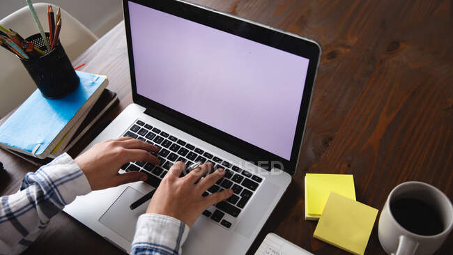 Über der Schulteransicht einer Frau, die zu Hause an einem Tisch sitzt, auf einem Laptop tippt und einen Stift mit Notizen, einer Tasse Kaffee, Büchern und Stiften auf dem Tisch neben sich hält. — Stockfoto