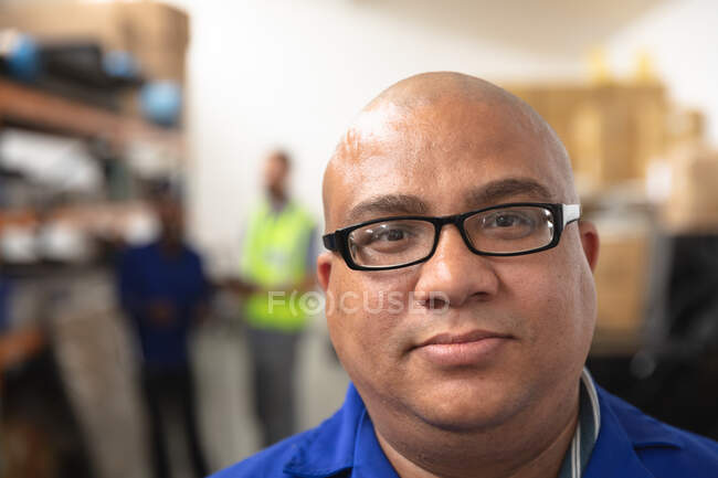 Portrait of a mixed race male worker wearing glasses in a storage warehouse at a factory making wheelchairs, looking at camera — Stock Photo