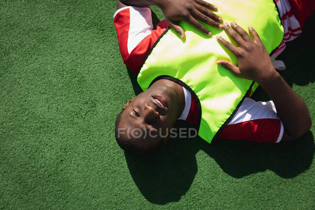 High angle front view of a teenage mixed race male field hockey player, lying down on a field hokey pitch, resting, focusing before a game on a sunny day — Stock Photo
