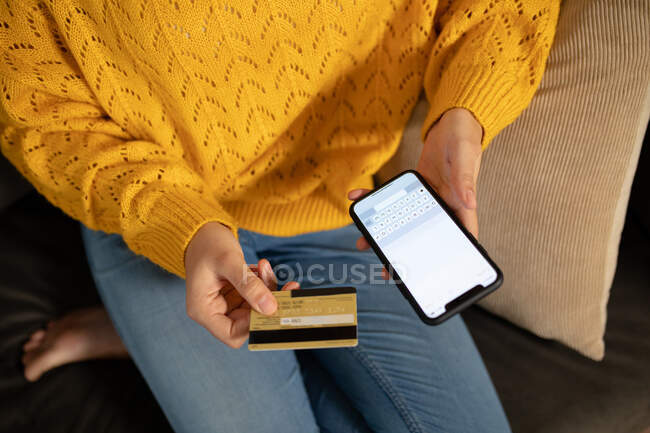 High angle mid section of woman relaxing at home, sitting on a sofa, holding a credit card and using her smartphone to make an online transaction — Stock Photo