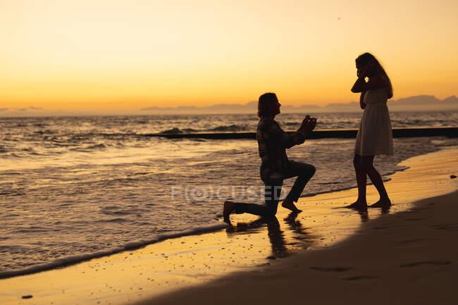 Кавказька пара проводить час на пляжі під час заходу сонця, а чоловік стоїть на колінах і пропонує жінці пропозицію. — стокове фото
