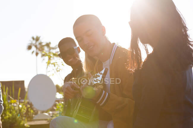 Front view of a multi-ethnic group of friends hanging out on a roof terrace on a sunny day, smiling, one of them playing the guitar — Stock Photo
