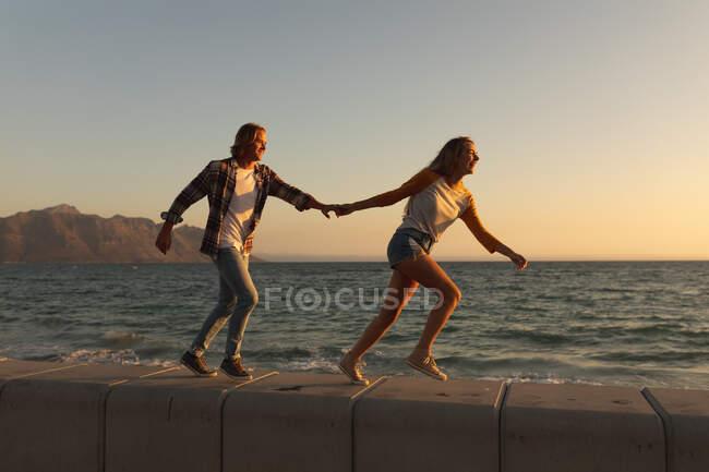 Coppia caucasica in vacanza al mare passeggiando sul lungomare durante il tramonto, tenendosi per mano, con cielo e mare sullo sfondo — Foto stock