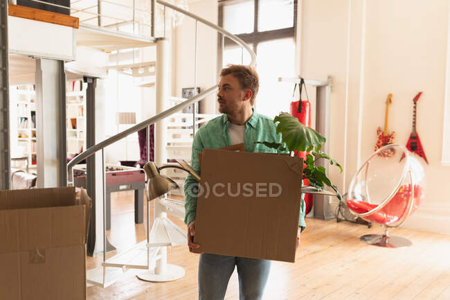 Front view of a young Caucasian man wearing green shirt, moving in to a new apartment, holding a cardboard box — Stock Photo
