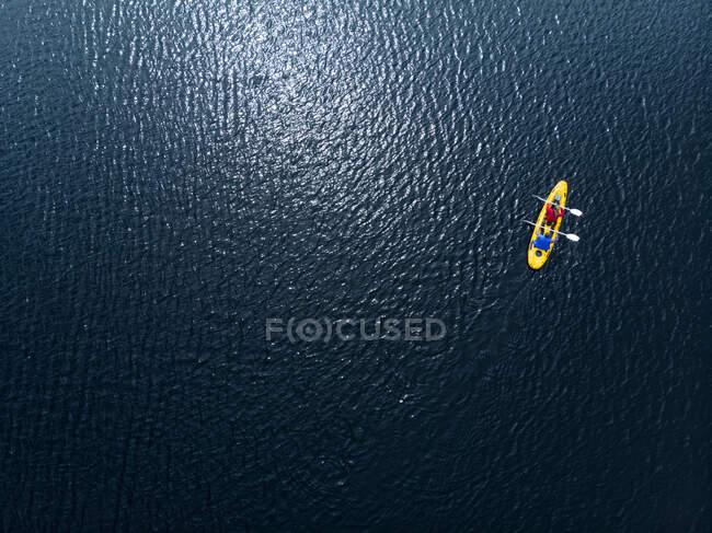 Drone colpo di una coppia caucasica kayak insieme in una barca gialla in acque calme, entrambi pagaiare con remi a doppia estremità — Foto stock