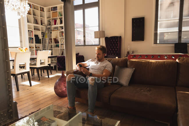 Front view of a young Caucasian man spending time at home, sitting on a sofa and using his smartphone. — Stock Photo