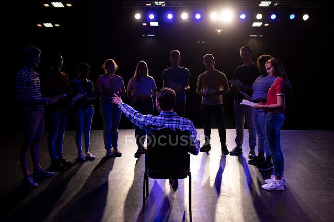 Veduta posteriore di un insegnante di liceo caucasico seduto su una sedia sul palco in un teatro scolastico vuoto e che indica durante le prove per uno spettacolo, preparando un gruppo multietnico di studenti delle scuole superiori adolescenti per uno spettacolo — Foto stock