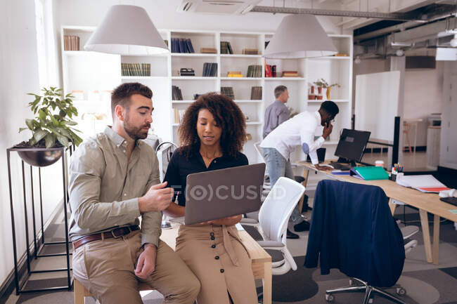 Una mujer de negocios de raza mixta y un hombre de negocios caucásico trabajando en una oficina moderna, usando una computadora portátil y hablando, con sus colegas de negocios trabajando en segundo plano - foto de stock