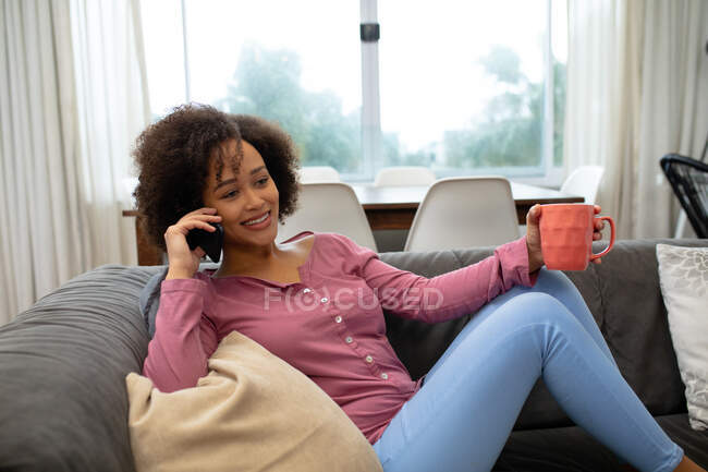 Front view of mixed race woman relaxing at home, sitting on a sofa with her legs up, talking on a smartphone, smiling and holding a cup of coffee — Stock Photo