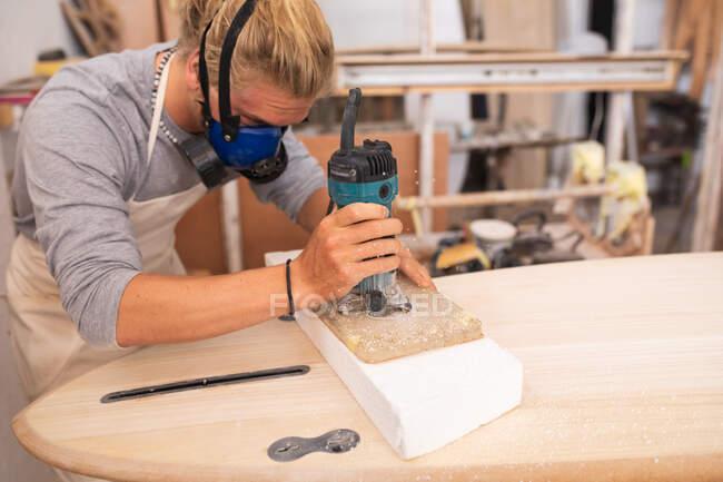 Белый мужчина-серфингист с длинными светлыми волосами, в маске для лица, работает в своей студии, делает доску для сёрфинга, шлифует ее поверхность шлифовальной шлифовкой. — стоковое фото