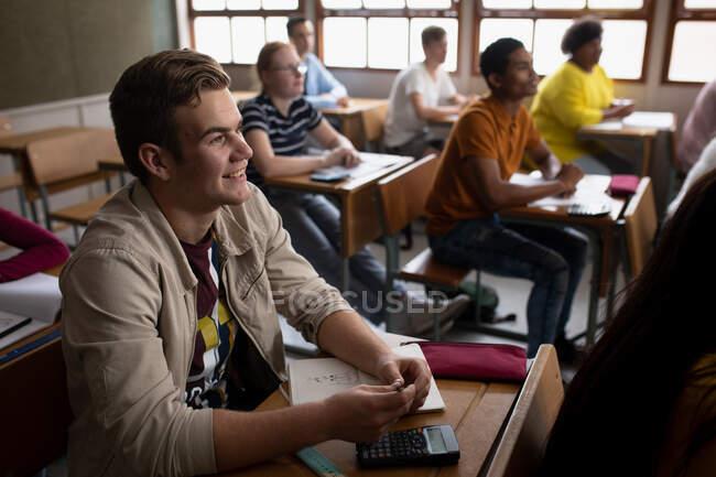 Vue latérale d'un adolescent caucasien dans une classe d'école assis au bureau, se concentrant et souriant, avec des camarades de classe masculins et féminins adolescents assis à des bureaux travaillant en arrière-plan — Photo de stock