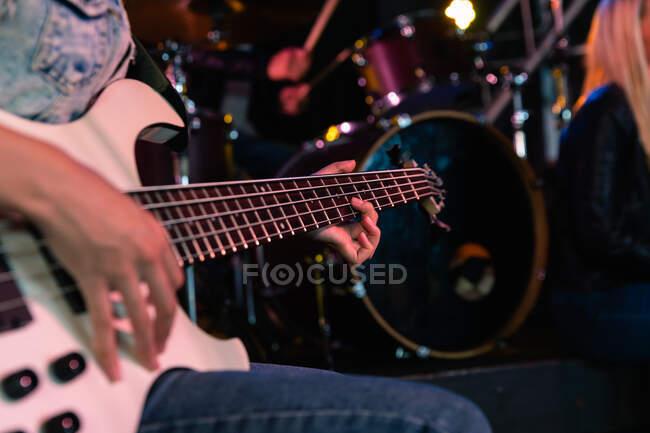 Seitenansicht der mittleren Sektion Nahaufnahme einer Bassistin, die vor einem Auftritt an einem Musikort probt, sitzt und ihre weiße Bassgitarre spielt, im Hintergrund ein Schlagzeug — Stockfoto