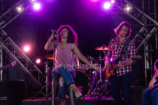 Vista frontal de una cantante femenina de raza mixta y un guitarrista masculino caucásico actuando en el escenario juntos en un lugar de música, la mujer sentada en un taburete, sosteniendo y cantando en un micrófono mientras el hombre toca la guitarra eléctrica - foto de stock