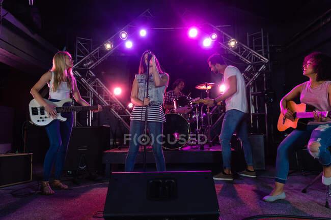 Vista frontal de un grupo multiétnico de guitarristas masculinos y dos femeninos y una cantante actuando en el escenario juntos en un lugar de música bajo luces rosadas, con un baterista masculino en el fondo - foto de stock