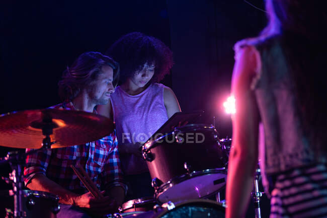 Frontansicht eines kaukasischen Mannes, der an einem Schlagzeug sitzt, und einer gemischten Frau, die neben ihm steht und gemeinsam auf einen Tablet-Computer schaut, während sie vor einem Auftritt ihr Bandequipment auf der Bühne eines Musiklokals aufbauen. — Stockfoto