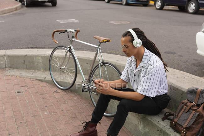 Vista laterale di un uomo di razza mista con lunghi dreadlocks in giro per la città in una giornata di sole, seduto in strada indossando le cuffie e utilizzando uno smartphone con la bicicletta accanto a lui. — Foto stock