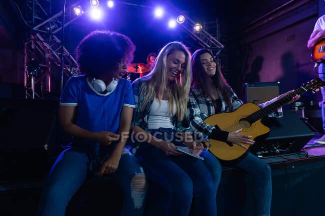 Frontansicht von drei Musikerinnen kaukasischer und gemischter Rasse, die sich vor ihrem Auftritt gemeinsam amüsieren, eine spielt eine Akustikgitarre, während eine lächelt und schreibt, während andere Musiker auf der Bühne im Hintergrund stehen. — Stockfoto