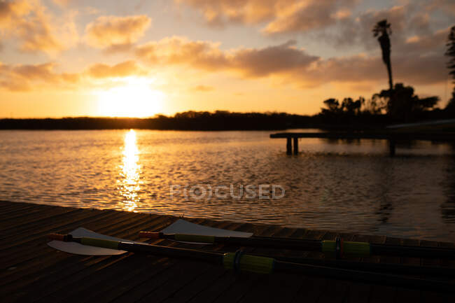 Stunning landscape of the river by twilight, with a jetty, lying oars left after rowing training, with clear sky, clouds and sun reflecting in water — Stock Photo