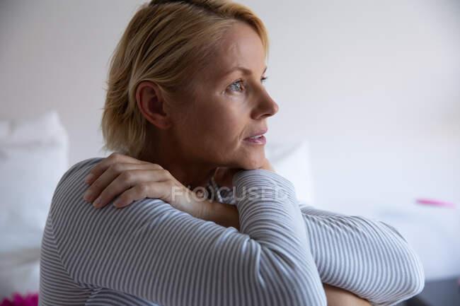 Vista lateral de una mujer caucásica disfrutando del tiempo libre en casa, sentada y pensando en su dormitorio, con las manos sobre los hombros - foto de stock