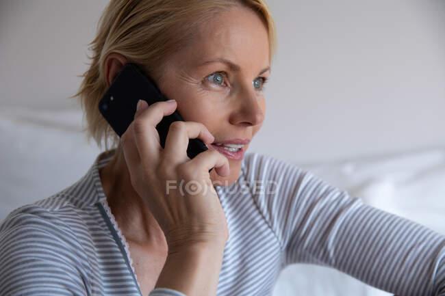 Vista lateral de uma mulher caucasiana desfrutando de tempo livre em casa, sentada em seu quarto, usando e falando em seu smartphone — Fotografia de Stock
