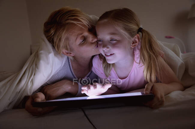 Front view of a Caucasian woman enjoying family time with her daughter at home together, lying on bed in their bedroom, smiling and using tablet computer — Stock Photo