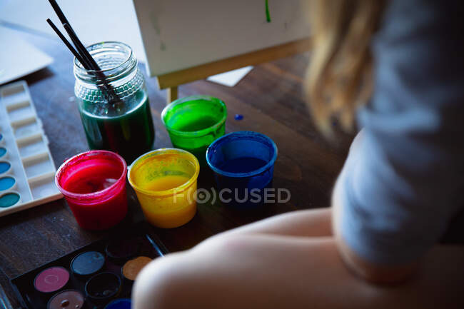 Rear view close up of girl enjoying free time at home, sitting on a table in a sitting room and painting with colorful paints — Stock Photo