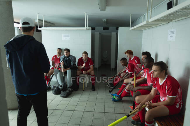 Rear view of a Caucasian male field hockey coach standing and interacting with a multi-ethnic group of teenage male field hockey players, sitting in a changing room listening to his instructions — Stock Photo