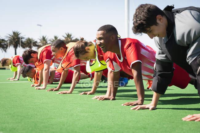 Vista lateral de um grupo multi-étnico de adolescentes jogadores de hóquei em campo treinando antes de um jogo, trabalhando em uma fileira, fazendo flexões em um campo de hóquei em um dia ensolarado — Fotografia de Stock
