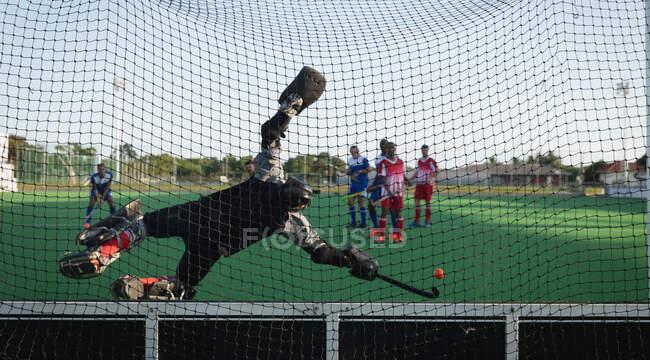 Задний вид на подростка Кавказский хоккей на траве вратарь в действии на поле, дайвинг, чтобы остановить мяч с хоккейной клюшкой, во время хоккейного матча между двумя многонациональными юношеских команд в солнечный день, видели через сетку ворот — стоковое фото